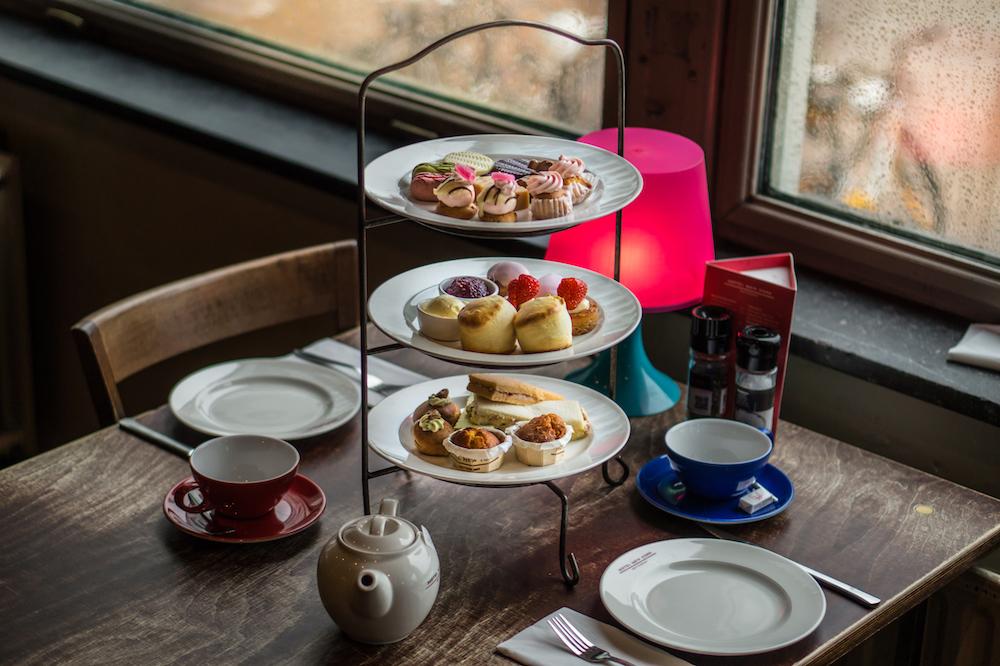 De afternoon tea van Hotel New York biedt alles wat je zou verwachten: scones met clotted cream, cakes, broodjes en natuurlijk een hoop thee.