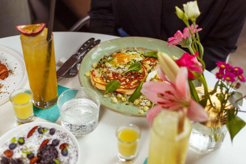 Je kunt terecht bij Ayla in Rotterdam voor brunch, lunch, borrels, diner of een drankje. Op hun lunchmenu staan lekkere sandwiches, gemaakt met desem brood door Das Brot. Een aantal voorbeelden van hun sandwiches zijn de Burrata met geroosterde kersttomaatjes en basilicum, de Gepekelde zalm met avocado, crème fraîche en atjar van rode kool en de Avocado met gepocheerd ei, saus romesco en za'atar.