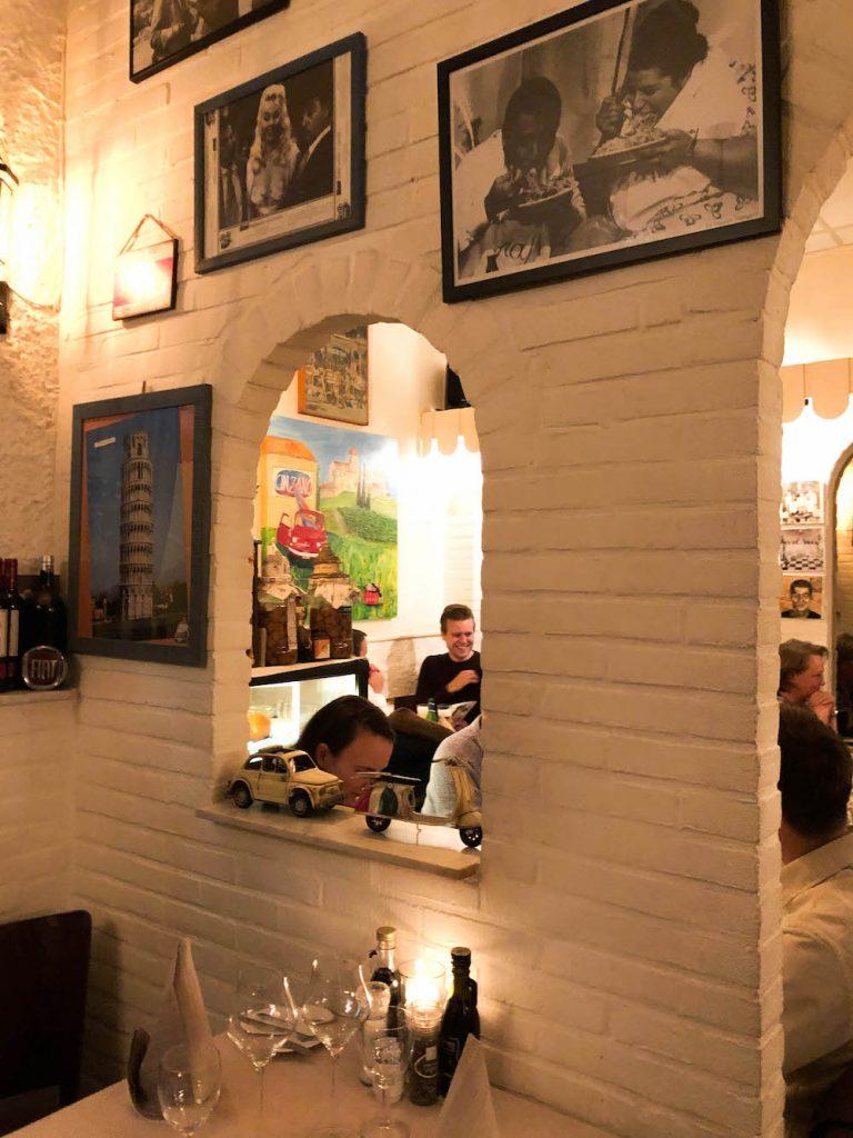 Het interieur van het gezellige Due Tonino. Er zitten schattige open raampjes in het restaurant en een hoop leuke Italiaanse details.
