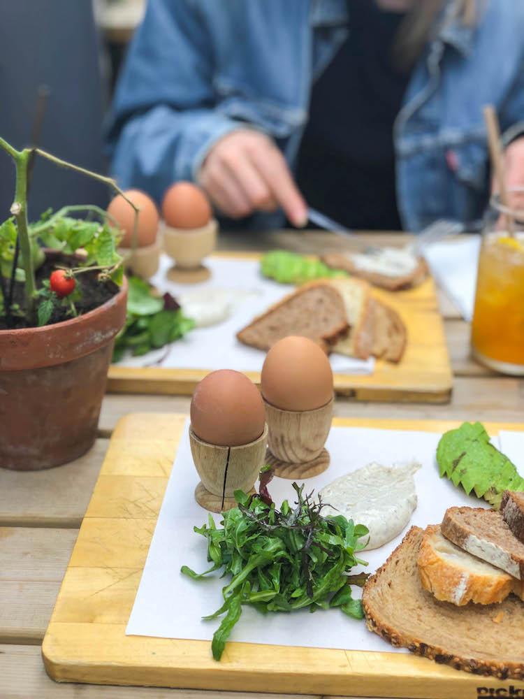 Een lekker ontbijtplankje bij Picknick in Rotterdam. Compleet met twee gekookte eitjes, verschillende broden, avocado en smeersels.