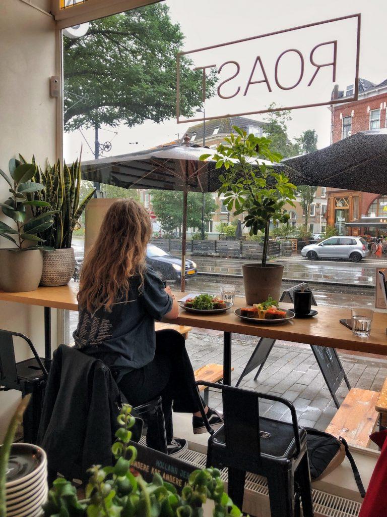 Roast is een gezellige hotspot op Middellandplein in Rotterdam West. Hier kun je speciality koffie drinken, maar ook matcha lattes, chai lattes en ook heerlijke lunch gerechten. Hier zitten we gezellig bij Roast bij het raam, te kijken naar de regen.