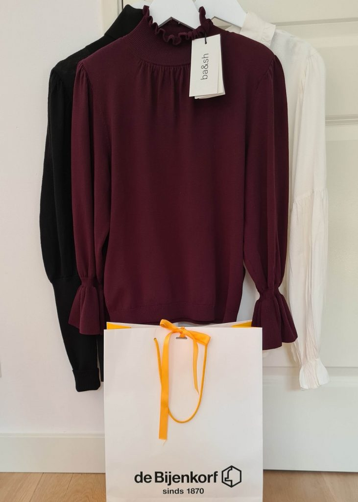 Jumper from designer ba&sh alongside a Bijenkorf shopping bag